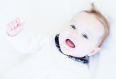 Happy laughing baby girl in a white knitted sweater Stock Photos