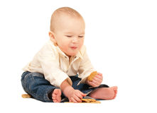 Happy laughing baby in jeans eating Royalty Free Stock Photo