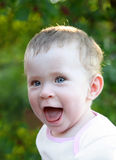 Happy laughing baby outdoor. On green background Royalty Free Stock Photo