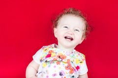 Happy laughing baby on a red blanket Royalty Free Stock Images