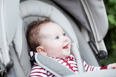Happy laughing baby sitting in a stroller. Happy laughing little baby sitting in a stroller Stock Photos