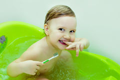 Happy laughing baby, taking a bath, brushing teeth. With toothbrush and toothpaste. A small child in the bathroom. Smiling toddler in bathroom with colorful Royalty Free Stock Photos
