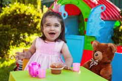 Happy laughing baby toddler girl playing in outdoor tea party with best friend Teddy Bear Stock Photos