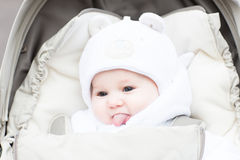 Happy laughing baby in a warm hat sitting in a stroller Royalty Free Stock Images