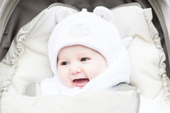 Happy laughing baby in a warm hat sitting in a stroller Royalty Free Stock Image