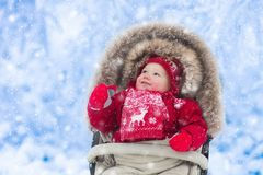 Baby in stroller in winter park with snow Stock Images