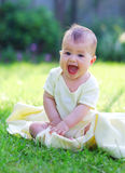 A happy laughing baby sitting on the blanket. A happy laughing baby in a yellow vest sitting on the blanket in the park Stock Image