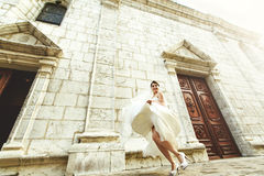 Happy laughing beautiful brunette bride dancing near old french Royalty Free Stock Images