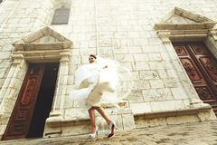 Happy laughing beautiful brunette bride dancing near old french Stock Photography