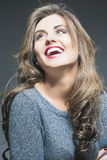 Happy Laughing Beautiful Young Woman  with Natural Brown Long Ha. Ir and Vivid Make up. Against Gray. Vertical Image Royalty Free Stock Images
