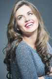 Happy Laughing Beautiful Young Woman  with Natural Brown Long Ha. Ir and Vivid Make up. Against Gray. Vertical Image Royalty Free Stock Photography
