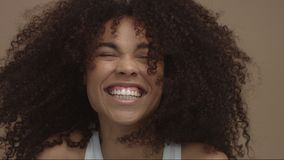 Happy laughing black woman with wind moving her cyrly hair