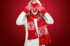 Happy laughing blond woman dressed in Christmas wear waitng gifts, isolated on red background Stock Photo