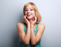 Happy laughing blond young woman holding hand at face Royalty Free Stock Image