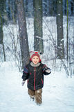 Happy laughing boy in a beautiful snowy winter forest Stock Photography