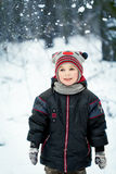 Happy laughing boy in a beautiful snowy winter forest Stock Photos