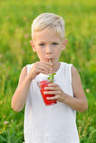 Happy laughing boy drinking a glass of red fresh juice watermelon. Summer time. Healthy lifestyle. Funny cute kid Royalty Free Stock Photography