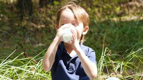 Happy laughing boy drinking milk or yogurt on nature background. Natural and healthy food for children. Slow motion stock video