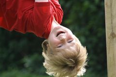 Happy Laughing Boy hanging upside down in a playground. A happy laughing boy hanging upside down in a children`s playground Stock Photo