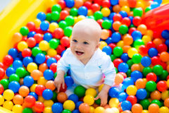 Child playing in ball pit on indoor playground. Happy laughing boy having fun in ball pit on birthday party in kids amusement park and indoor play center. Child royalty free stock photos
