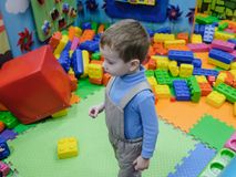 Boy having fun in kids amusement park and indoor play center. Child playing with colorful toys in playground. Happy laughing boy having fun on birthday party in Royalty Free Stock Image