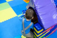 Boy having fun in kids amusement park and indoor play center. Child playing with colorful toys in playground. Happy laughing boy having fun on birthday party in Stock Photography