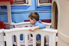 Boy having fun in kids amusement park and indoor play center. Child playing with colorful toys in playground. Happy laughing boy having fun on birthday party in Royalty Free Stock Photos