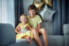 Happy laughing boy and his baby sister pose on sofa. Indoors stock images