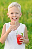 Happy laughing boy holding a glass of red fresh juice watermelon. Summer time. Healthy lifestyle. Funny cute kid Stock Photos