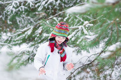 Happy laughing boy playing in a snowy forest Royalty Free Stock Image