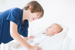 Happy laughing boy talking to newborn baby brother Stock Image