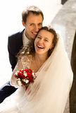 Happy laughing bride and groom on street at sunny day Stock Photo