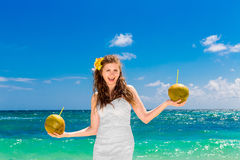 Happy laughing bride having fun on a tropical beach holding a tw Royalty Free Stock Image