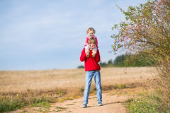 Happy laughing brother and his baby sister in field Royalty Free Stock Photography