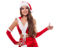 Happy laughing brunette woman dressed as Santa pointing at us, i Stock Photos
