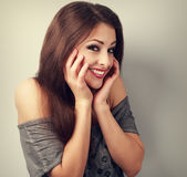 Happy laughing brunette young woman holding the hand at face and Stock Image