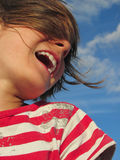 Happy laughing child against blue sky Stock Image