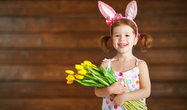 Happy laughing child girl in bunny ears with  yellow tulips on. Happy laughing child girl in bunny ears with  bouquet of yellow tulips on wooden background Stock Photography