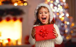 Happy laughing child girl with christmas present. At home stock photos