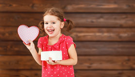 Happy laughing child girl with gift Valentine`s Day, wooden Royalty Free Stock Photo