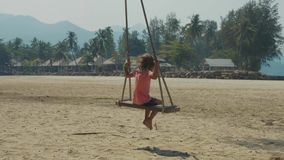 Happy laughing child girl swinging at tropical sandy beach with funny emotions. Cheerful baby amuses at island`s beach stock video