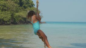 Happy laughing child girl swinging at tropical sandy beach with funny emotions. In slow motion. Cheerful baby amuses at island`s beach stock video footage