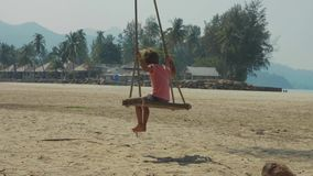 Happy laughing child girl swinging at tropical sandy beach with funny emotions. In slow motion. Cheerful baby amuses at island`s beach stock video