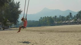 Happy laughing child girl swinging at tropical sandy beach with funny emotions. In slow motion. Cheerful baby amuses at island`s beach stock footage