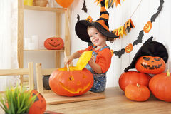 Happy laughing child girl in a witches hat cut a pumpkin for Hal Stock Images