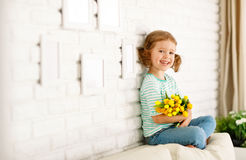 Happy laughing  child girl with  yellow tulips at home Royalty Free Stock Images