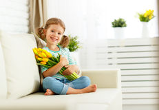Happy laughing  child girl with  yellow tulips at home Stock Photography