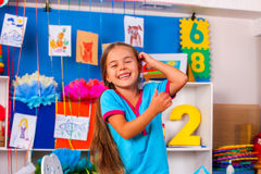 Happy laughing child in preschool class. Interior of game room in preschool kindergarten with little girl child. Happy laughing child in preschool class stock image
