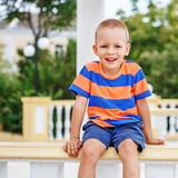 Happy laughing child spends summer in the city Royalty Free Stock Image