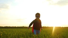A happy laughing child in a superhero costume runs across a green field or meadow. His face is illuminated by the rays